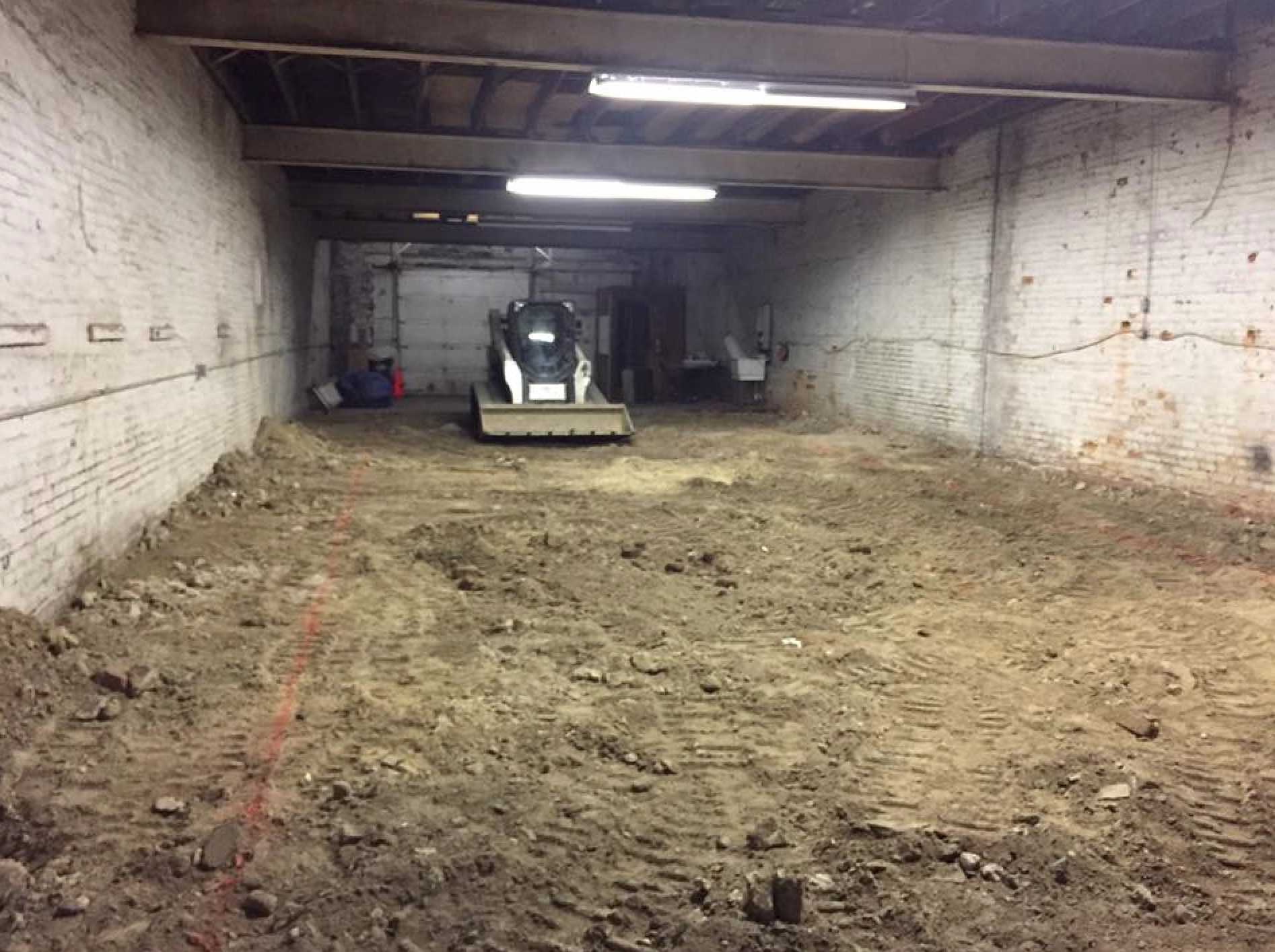an earth-mover sits motionless in a garage with a dirt floor